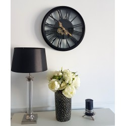 Czarny zegar ścienny z widocznym ruchomym mechanzmem